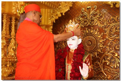 Acharya Swamishree presents a gold crown to Lord Swaminarayan