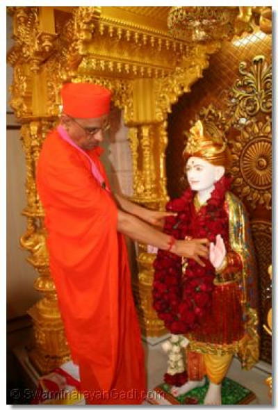 Acharya Swamishree offers a garland of roses to Jeevanpran Abji Bapashree