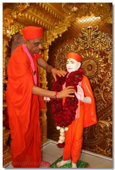 Acharya Swamishree offers a garland of roses to Jeevanpran Shree Muktajeevan Swamibapa