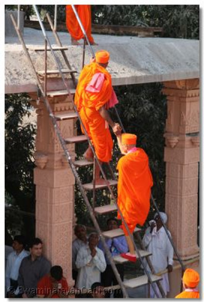 Acharya Swamsihree climbs to the top of the temple to install the new flags