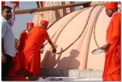 Acharya Swamishree consecrates the flag before it is raised on the domes of the new temple