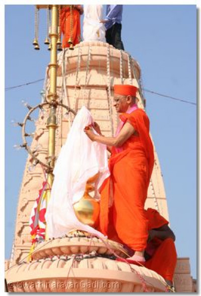 Acharya Swamishree unviels the golden kalashes on the peaks of the temple domes