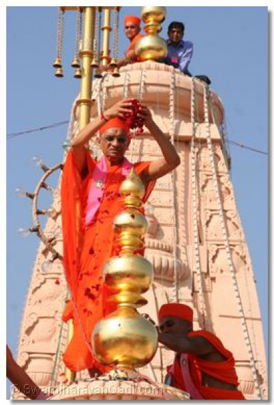 Acharya Swamishree scatters rose petals over the new kalash at the top of the temple