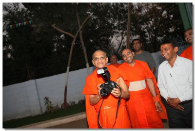 Acharya Swamishree consecrates a new camera bought to capture the memories of the festival
