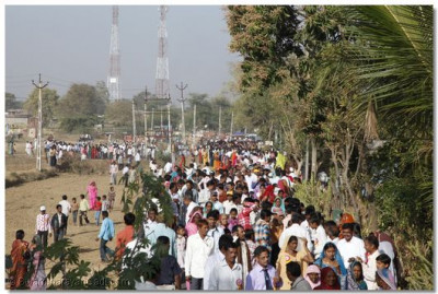 Many thousands of disciples line the pathway to the Mandir