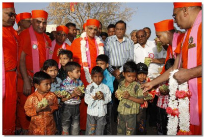 Acharya Swamishree distributes fresh fruit to the children of Panchmahal