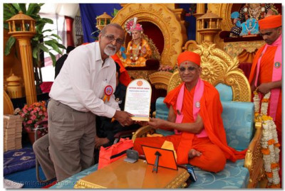 Acharya Swamishree receives a memento from Action Group India