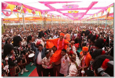 Acharya Swamishree is carried by disciples to the stage as thousands of people cheer with joy