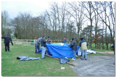A team starts building a tent