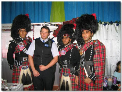 A Community Support Officer poses with members of Shree Muktajeevan Pipe Band