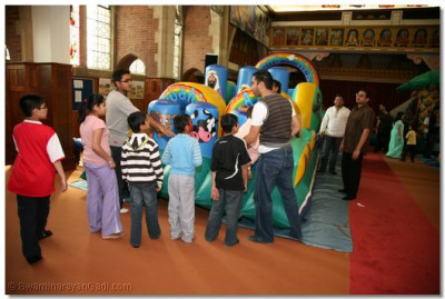 Children queue to use one of the bouncy castles
