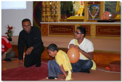 A young member of Team Shreeji Maharaj attempts to pop the balloon