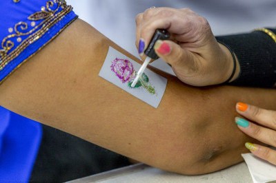 A variety of glitter tattoos are applied to participants