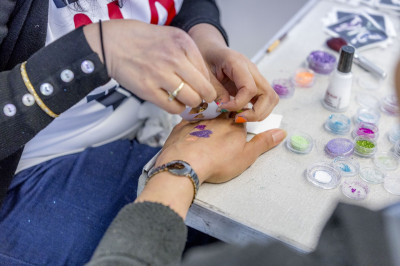 Glitter tattoos are applied to participants