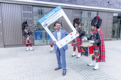 Councillor Muhammed Butt poses with the twitter board as Shree Muktajeevan Swamibapa Pipe Band perform
