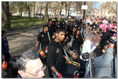 Dhol players perform as the runners go past