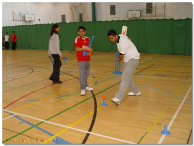 A cricket coach demonstrates batting