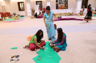 Disciples make rangoli patterns to be placed within the annakut display