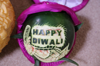 Disciples intracately and maticulously carve Happy Diwali into the skin of a watermelon