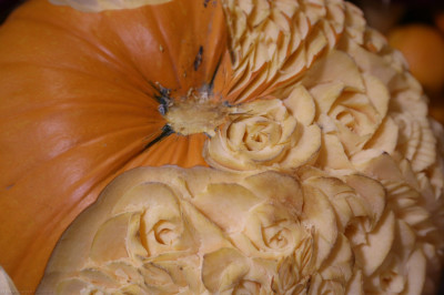 Disciples carve rose patterns into one side of a pumpkin