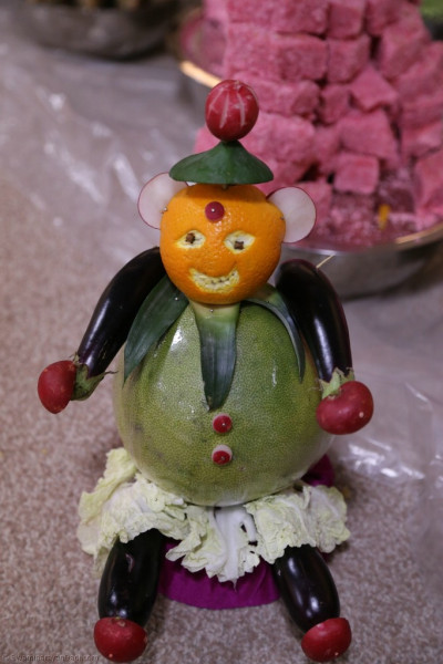 A close up of another character carved from fruit and veg