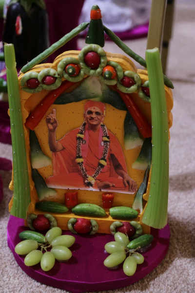 Divine darshan of His Divine Holiness Acharya Swamishree within a beautiful frame crafted using fruit and vegetables