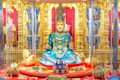 Shree Ghanshyam Maharaj seated in a vault surrounded by jewellry