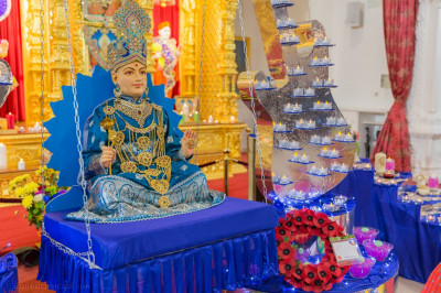 Shree Ghanshyam Maharaj seated at the centre of the grand musical themed swing