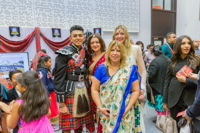 Visitors dressed in sarees take a photo with a band member