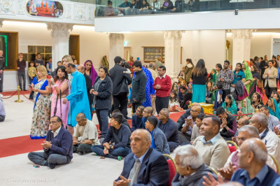 Visitors attend the evening sabha in Mandir