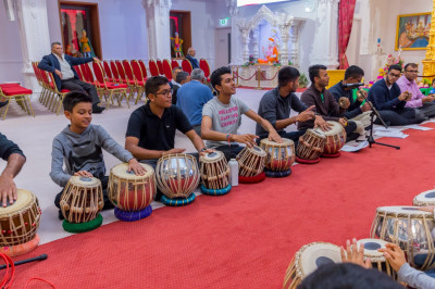 Young disciples of Shree Muktajeevan Swamibapa perform tabla as disciples sing devotional songs and play hand cymbals