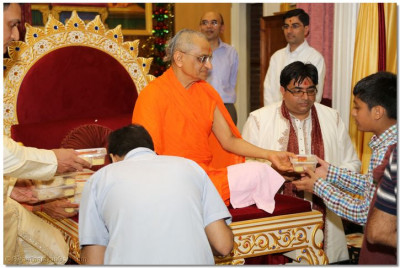 His Divine Holiness Acharya Swamishree gives prasad to all