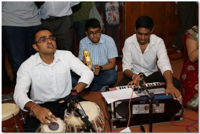 Disciples play traditional Indian musical instruments to accompany the medley of devotional songs to please Lord Shree Swaminarayanbapa Swamibapa