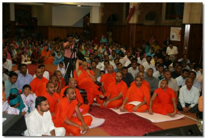 Acharya Swamishree, sants, and disciples watch the performances