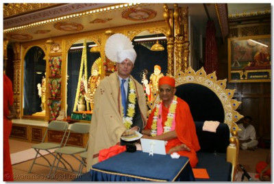 Cllr Mike Freer receives a prasad pagh and shawl from Acharya Swamishree