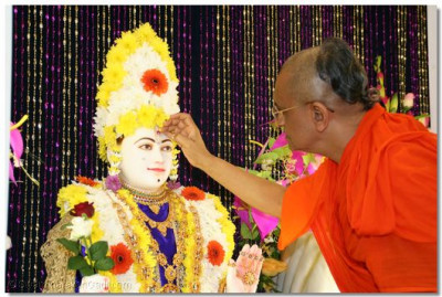 Acharya Swamishree impresses a chandlo on Shree Ghanshyam Maharaj
