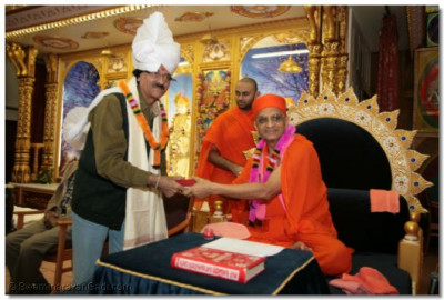 Acharya Swamishree blesses honoured guests with prasad pagh and shawls