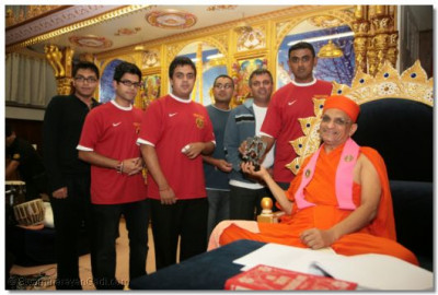 Members of Shree Muktajeevan Sports Academy receive a memento from Acharya Swamishree