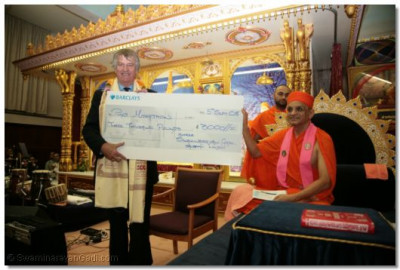 Acharya Swamishree presents a cheque to Ed Stuart of the Phab kids charity