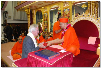 Acharya Swamishree offers prasad to Cllr. Jim Tierney, London Borough of Barnet