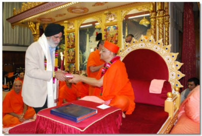 Acharya Swamishree offers prasad to Cllr. Harbhajan Singh, London Borough of Brent