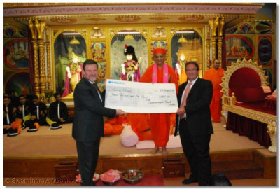 Acharya Swamishree presents a cheque of �12,000 to Rt Hon Tony McNulty and Mr Barry Gardiner MP. The money was raised by members of the Temple for Sports Relief.
