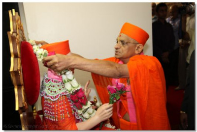 Acharya Swamishree places a rose garland on Jeevanpran Swamibapa before the start of the procession
