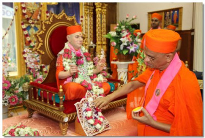 Acharya Swamishree puts chandan on Shree Harikrishna Maharaj