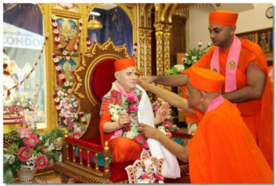 Acharya Swamishree places a dhoti on Jeevanpran Swamibapa