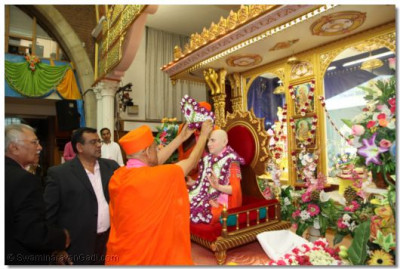 A flower 'moogat' is placed on Jeevanpran Swamibapa by Acharya Swamishree