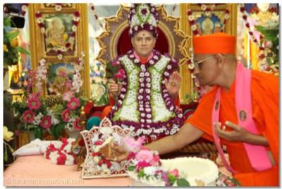 Acharya Swamishree offers prasad cake to Shree Harikrishna Maharaj