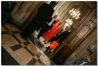 Acharya Swamishree walks through the corridors of House of Commons towards the reception room