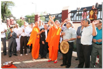Acharya Swamishree performs aarti during the flag raising ceremony