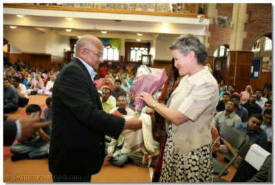 Mrs Brigid Martin is presented with a shawl and flowers by temple trustee Mr Premjibhai Varsani